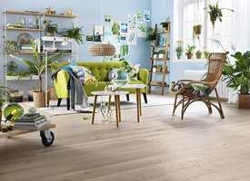 <b>LENES FAVORITT:</b> Av tregulv er det eikeparketten My Heritage fra Tarkett. Her er den i fint samspill med lyseblå vegger, grønn sofa. Og prikken over i-en er en bitteliten dasj knall rosa. (Foto: Tarkett)