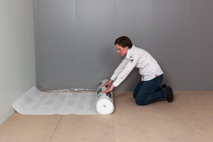 Mellom parketten og undergulvet skal det alltid brukes et gulvunderlag. Dette kan være laget av ullpapp eller skumplast, ha fuktsperre, og kan gi trinnlydsdemping – det finnes mange varianter underlag til gulv. Her legger Ylva Kleiven underlagsskum.