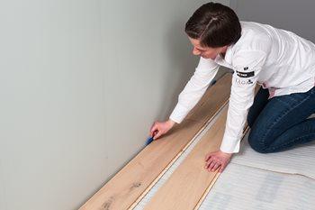 Tre er et hygroskopisk materiale, som krymper og utvider seg i takt med endringer i luftfuktigheten. Dette gjelder også parkettgulv, og derfor skal det alltid være en liten avstand mellom veggen og gulvet. Ylva Kleiven bruker små plastkiler for å lage bev