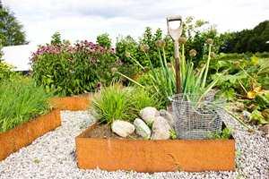 <b>MATERIALMIKS:</b> Elvegrus, rustent stål og rullestein skaper vakker kontrast til alt det grønne.