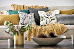 <b>TEKSTILER:</b> En fargeløs sofa kan piffes opp med tekstiler i solfargen, og myke pledd og puter blir ekstra innbydende. Tekstiler fra Sanderson, kolleksjon Embeton Bay. Føres av Intag.