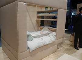 <b>HULE:</b> Ytterveggene på sengen var polstret og trukket med et grovvevet tekstil i grå-rosa sjatteringer.