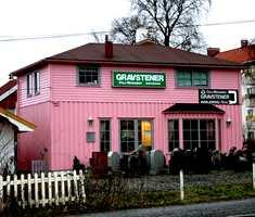 Fargekombinasjonen rosa og grønt stemmer ikke med virksomheten som holder hus her: Mange vil mene at salg av gravsteiner krever mer behersket fargebruk.