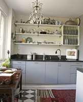 I begynnelsen var kjøkkenet grått. Det første Ellen gjorde da hun flyttet inn var å fjerne overskapene og sette opp hyller isteden. Her fikk det fineste serviset plass. Underskapene fra Sigdal ble malt i en kraftig gråfarge (S 4500-N). Den nye benken er i blank, svart stein.