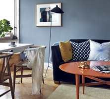 Det oransje bordet og den gule puten står i kontrast til blåtonene.