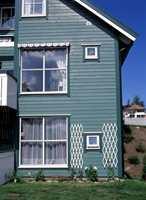 For å skjule deler av huset, kan du velge to farger som glir over i hverandre. Her er overgangen mellom vindu og vegg myk: grønn hovedfarge med mørkere grønne vinduer. Det hvite, derimot, gir en markant overgang.