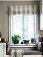 PLASS FOR TO: Benken er en del av kjøkkeninnredningen, hyggelig plassert foran vinduet. Arbeidsbenker i normal høyde på begge sider. Puter og pledd myker opp blant de rette linjene.