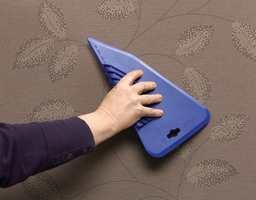 Sikre god vedheft og ved å stryjke ut luftbobler fra midten og ut.