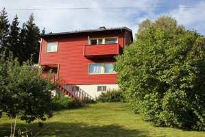 <b>RØDT OG GULT:</b> Det er ingen regel at røde hus skal ha hvit staffasjefarge. Her markerer gult vinduene fint, og skaper en rolig helhet.