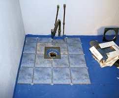 Legging av gulvflisene etter at det er pålagt blå membran.