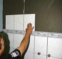 Påsetting av veggfliser hvor veggen er delt med en bord.