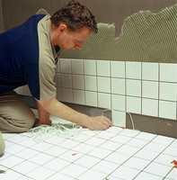 i hjørnet mellom vegg og gulv kan du bruke en stopper for å unngå at nederste flisrad siger og gir ujevne fuger.