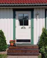 Hvit fasade, hvit dør, men en grønn staffasjefarge som gir litt mer liv.
