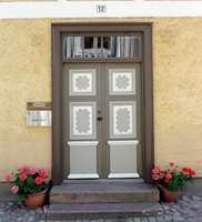 Klassisk dekorativ dør på et eldre murhus. Det er brukt fire forskjellige farger på dørpartiet, men fargene matcher.