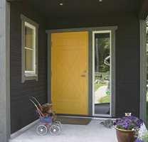 Et nytt hus hvor døren skiller seg ut fra den mørke fasaden og den naturtro grønne på listene.