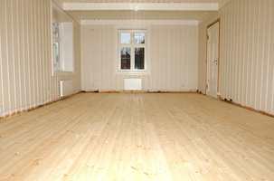 I dette rommet valgte man å legge nytt tregulv. Furubordene ble spesialbestilt i samme bredde som eksisterende gulv i et tilstøtende rom.