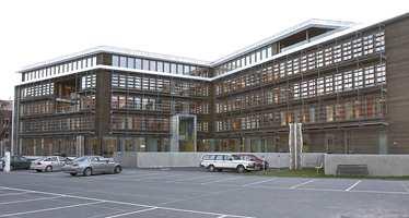 Husbankens fasader er kledd med jernvitrolbehandlet malmfuru. Den utvendige solavskjermingen er i aluminium.