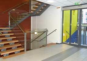 Blå og syrliggrønne dekorasjoner i inngangspartiet står som frekk kontrast til en lun trappeoppgang der eiketrinnene har fått en mørk kantmarkering.