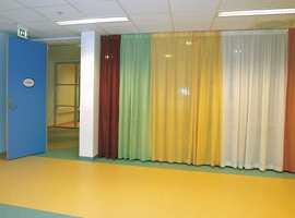 Aktivitetsrom i 1. etasje hvor fargene på vinylbelegget er tatt opp igjen i gardinene.