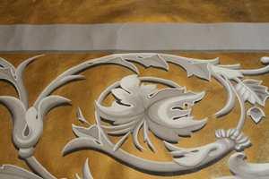 Detalj av linlerret forgylt med slagmetall. Dekoren er malt med linoljemaling som en illusjon av stukkornamenter. Lerretene ble montert på finer og dekker gallerifrontene i gamle Drammen teater.