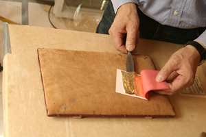 Med den flate gullkniven løftes det tynne bladgullet opp fra arket.
