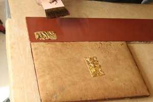 Gullet er plassert  på det preparerte treet som skal forgylles, hvor det festes med spesialpensler og poleres med agatstein.