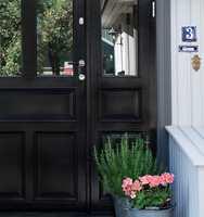 NESTEN SORT Døren er så mørk (970 Mørk Brun) at den ser sort ut, men er ikke like hard som sort kan være. Grå omrammimg (954 Aske/S 7502-Y) gir myk overgang til fasadefargen. (Foto: Butinox Futura)