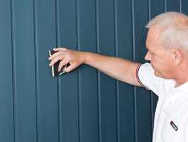 Slip lett over veggen med en slipepute eller slipepapir.