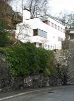 Hvit murvilla i Bergen tegnet av arkitekt Leif Grung i 1934. Pipen er plassert som et dekorativt element i hjørnet.  Stuen har store hjørnevinduer, men toppetasjen har tofags vinduer typisk for mindre rom.