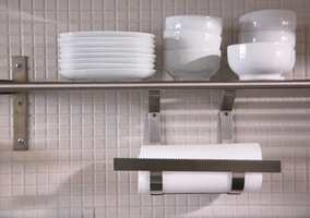Veggen på kjøkkenet har glassmosaikkfliser i hvitt og åpne hyller for servise.