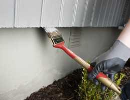 Det er lett å søle nedover på grunnmuren når du maler veggene.