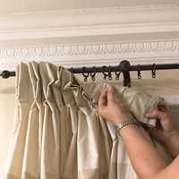 Ringene på smijernstangen er festet i hekter på baksiden av gardinen.