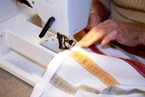 Beregn ca.1,5 cm til kant øverst. Brett inn og stryk. Sy deretter fløyelsdelen av borrelåsen ca. 0,5 cm inn på stoffet.