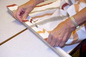 Fest stoffet til toppskinen ved hjelp av borrelåsen og monter festet for gardinsnoren i ønsket høyde. Rull'n inn...