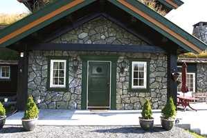 Hytte 1 - i kombinasjon av malt treverk og stein.