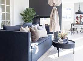 <b>MØRK VEGG</b> Peisveggen er malt i en mørk farge, som står fint til møblene; Classico kalkmaling fra Pure & Original, farge Black Smoke.