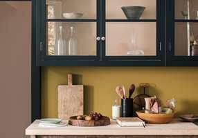 <b>SOFISTIKERT</b>Kjøkkenskapene i en mørk gråfarge, mot rosa og gult med mye sort i. (Foto: Nordsjö)