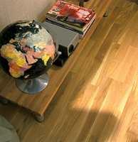 Gulvet er i lys oljet eik. Det lave bordet med stålbein har eikeplate. Det lave bordet fungerer som en praktisk oppbevaringsplass for magasiner