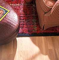 Pallen som er trukket med blankt skinn er en spennende kontrast til de lune og varme overflatene i gulv, teppe, og møbelstoff.