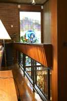 Rekkverket i stuen før. Blomsterkassen på toppen av smijernsrekkverket var i grell 60-tallsstil. Sammen med blyglassvindu og mursteinsvegg ble det for mye.
