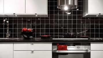 Sorte fliser med hvit fug i kontrast gir et tøffere utseende til kjøkkenet. Fra Golvabia.