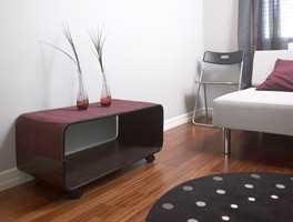Møbler og tepper har mørke farger. Burgunder er hentet fra stripene i gardinen.