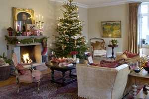 Den vakre peisestuen er pyntet til julefest. Myke stoffer, engler og lys skaper den gode stemningen.