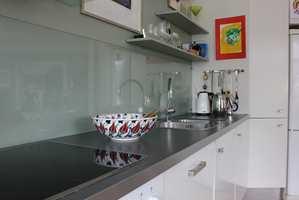 <b>GLASSPLATE:</b> Veggen er malt helt ned til kjøkkenbenken. Den malte veggen skjermes mot sprut fra kokesone og vask med en glassplate som er montert over benken.