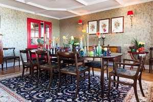 GULLSTUE: Alle rom har sin karakter. I spisestuen er veggene kledd med gulltapet med fugler på grønne grener. Den røde døren mot kjøkkenet har farge fra innebygde vitrineskap på motsatt vegg. Bordpynt, tepper og møbler er gjenbruk og kommer fra fjern og nær.