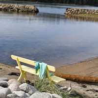 På en gulmalt benken på stranda.. Utemøbler som er litt utgått på dato, får nytt liv med noen strøk med maling. Denne er malt med maling fra Nordsjö.