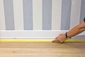 Press tapen godt inntil gulvlisten nederst mot gulvet, så unngår du at malingen trekker opp på listen.