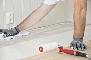 Det nyslipte gulvet ble farget med hvitpigmentert olje. Etterpå ble det lakkert med matt gulvlakk.