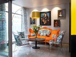 Gulmalte søyler, laserskårede skillevegger, oransje møbler og puter i et frekt stoff fra Jean-Paul Gaultier er noen av de mange fargene og materialene i resepsjonen.