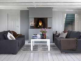 Gulvet er patinert eik som kler de rustikke bygningsdetaljene, og peisen og brannmuren ble malt i en varm gråtone og glir inn i rommet øvrige fargeskala.